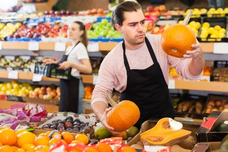Glad man with pumpkin in hands wearing apron on the supermarket