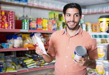 Joyful man is choosing conserved peas with help note list in market Standard-Bild