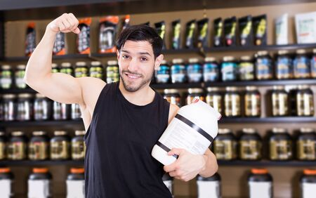 happy active muscular man showing his biceps and holding pot of  sport nutrition in shop Stock Photo