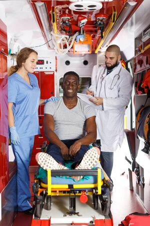 Smiling afro man sitting on stretcher near two emergency doctors in ambulance car