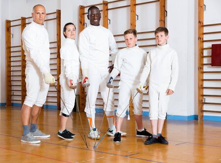 Group portrait of young happy positive fencers with coaches holding rapiers in training room