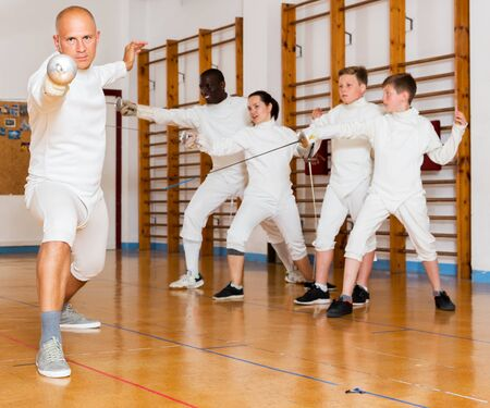 Male athlete training attack movements with rapier at fencing workout