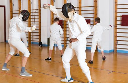 portrait of athletes at fencing workout, exercising attack movements in duel