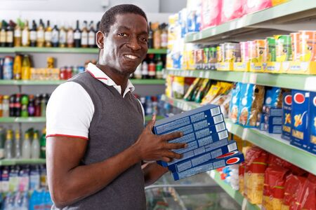Portrait of African man buying pasta in supermarket