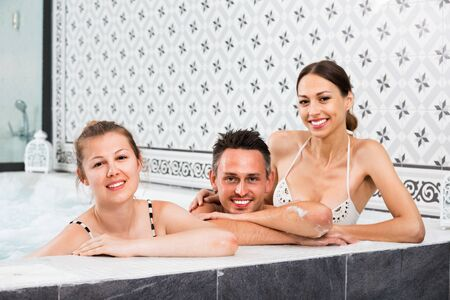 Three  positive friends relaxing at spa, enjoying company