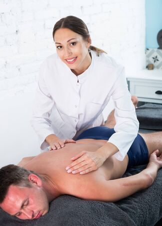 Professional masseuse performing back massage to male client in spa center Stock Photo
