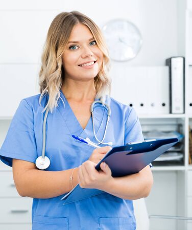 Doctor girl stands near a table in the office