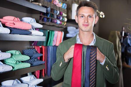 Smiling guy choosing new tie in male cloths store