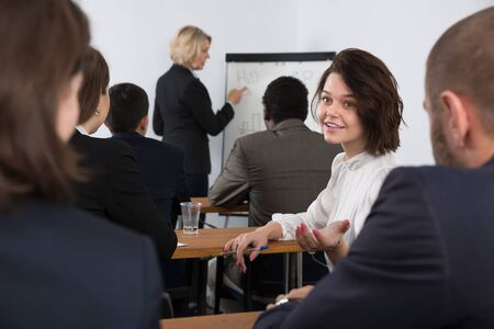 Young positive woman turning to other participants during business training in conference room