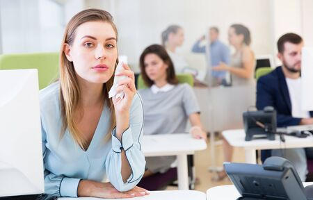 Portrait of upset young woman foreground in busy open plan office Archivio Fotografico