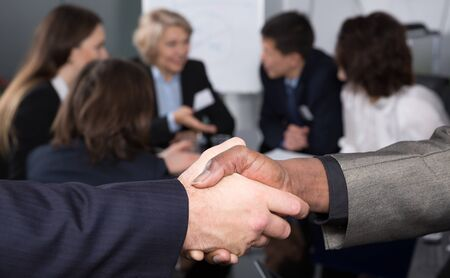 Strong handshake of businessmen confirming successful business partnership