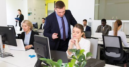 Irritated boss scolding female subordinate pointing out shortcomings and misses in work