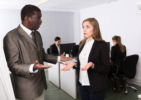 Irritated boss scolding female subordinate in modern office, pointing out shortcomings in work
