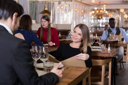 Elegant young woman sitting with male friend at table in restaurant, discussing menu Imagens