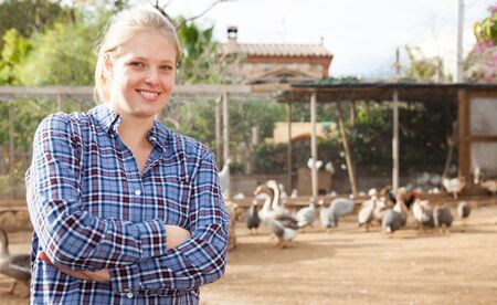 Portrait of smiling and confident young female farmer on poultry yard on background with domestic fowl Stock Photo