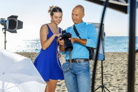 Photographer reviewing photos and talking to female model during photo shoot on sunny seashore Imagens