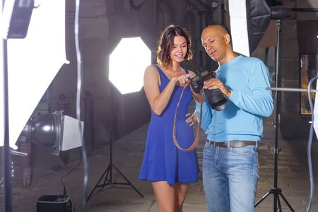 positive photographer and model discussing picture on camera display during photo session on city street Imagens
