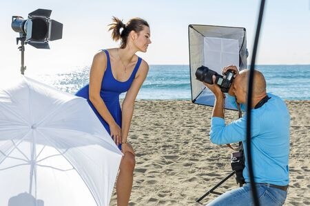 Professional photo shooting outdoors. positive female model posing to professional photographer on sunny beach