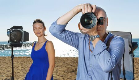 Portrait of professional cheerful positive smiling photographer looking through camera lens during shooting on sunny beach
