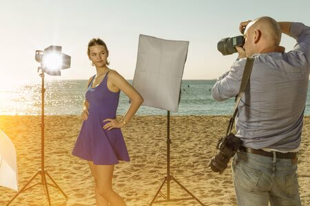 Professional photo shooting outdoors. Attractive female model posing to professional photographer on sunny beach