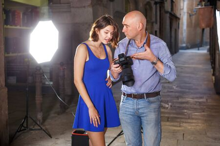 Professional photographer showing photos on digital camera to smiling model girl during shooting on the old city street