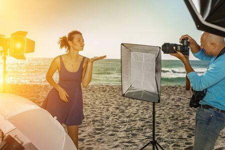 Photo shoot of glad model with professional photographer on sea coast Imagens