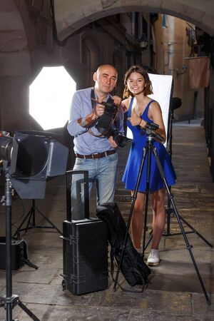 cheerful female model and photographer standing among professional photo equipment during photo shooting on town street Imagens
