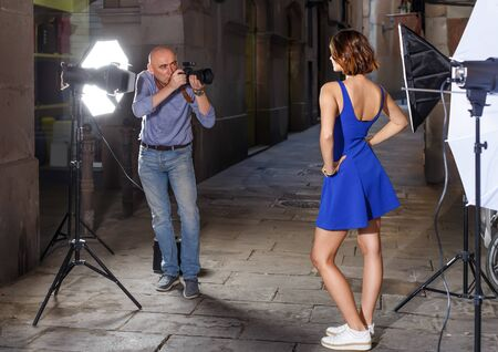Professional photo shooting outdoors. Professional man photographer working with model on city street
