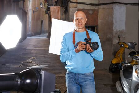 Portrait of male photographer standing with camera among professional photo equipment on old city street