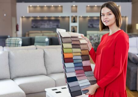 Friendly sales consultant demonstrating samples of upholstery fabric at furniture shop