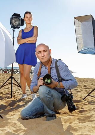 Portrait of cheerful  smiling male photographer with camera among professional photo equipment on seaside