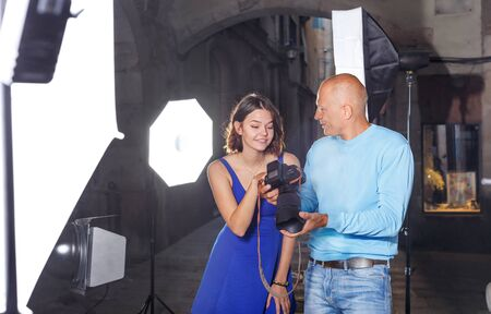 Professional photographer showing photos on a digital camera to smiling model girl during shooting at a old city street Imagens