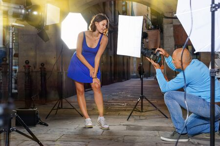 Professional photo shooting outdoors. Attractive  pleasant beautiful positive female model posing to photographer on city street Imagens