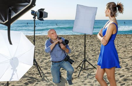 Positive professional photographer shooting young female model on seaside in sunny day Imagens