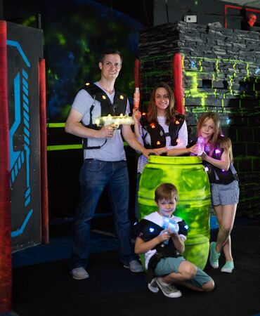 Group of happy kids and adults with laser guns posing together while having fun on dark lasertag arena
