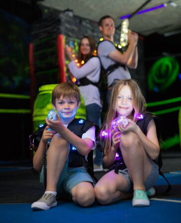 Portrait of happy kids sitting with laser guns during laser tag game with parents in dark room