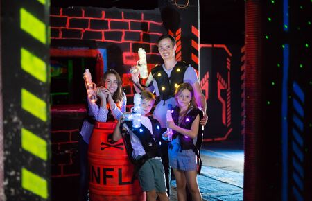 Portrait of happy kids and theirs parents with laser guns during lasertag game in dark room