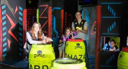 Portrait of happy young woman playing laser tag in dark labyrinth with her friendly family