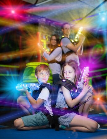 Two little confident laser tag players sitting back to back with guns on gaming arena in bright beams of laser gun Imagens