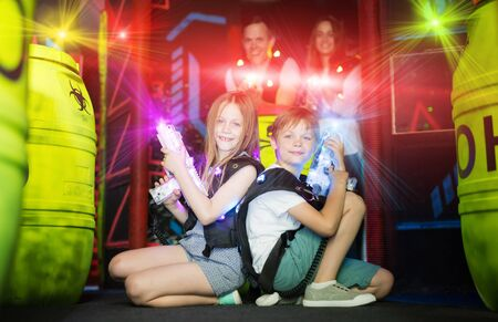 Happy little brother and sister sitting back to back in colorful laser beams holding laser guns during lasertag game with family in labyrinth