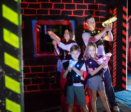 Group of happy kids and adults with laser guns having fun on dark lasertag arena Imagens