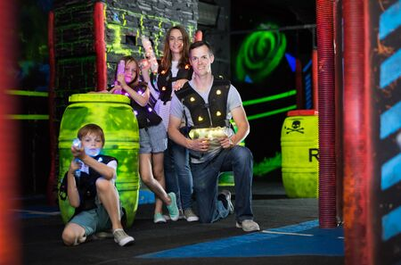 Modern young parents and children with laser pistols posing together in dark laser tag labyrinth