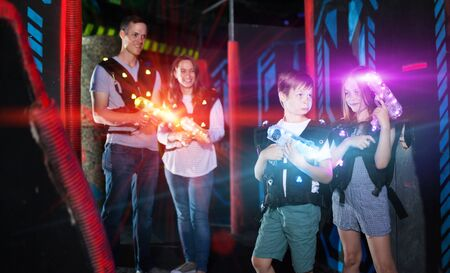 Portrait of excited kids in bright beams of laser guns during laser tag game in dark room with parents Imagens