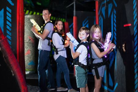 Cheerful little boy and girl standing back to back with laser pistols in dark lasertag room during game with parents 版權商用圖片