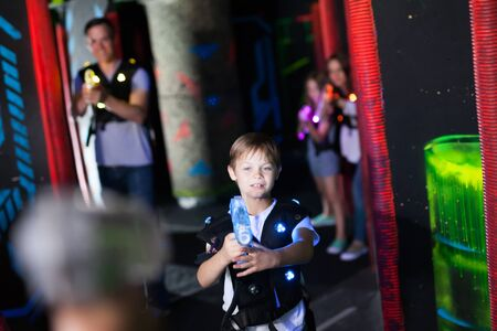 Little boy aiming laser gun at another player during laser tag game in dark labyrinth Imagens