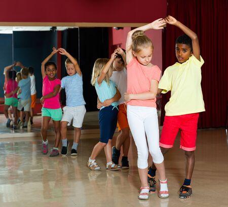 Happy kids dancing salsa dance in modern studio
