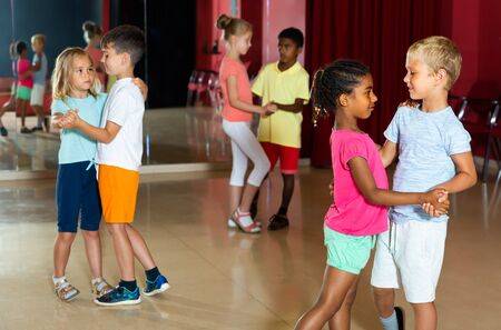Group of positive kids dancing salsa dance in modern studio