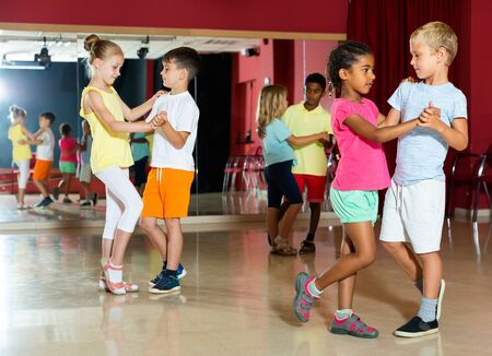 Group of cheery children dancing salsa dance in modern studio Stockfoto