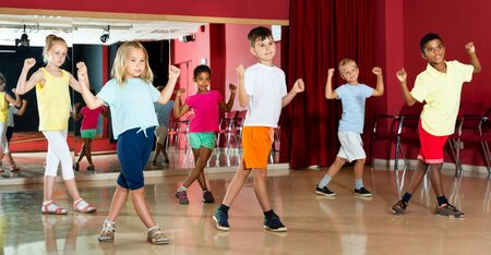 Group of smiling little boys and beautiful girls having a dancing class at the studio
