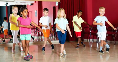 Positive happy cheerful smiling children studying modern style dance  in class indoors
